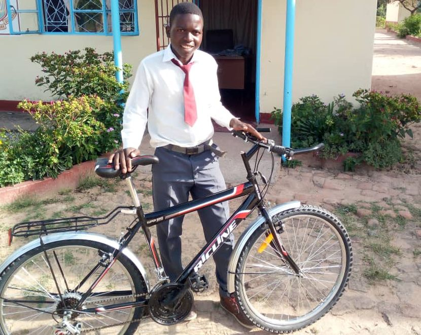 A volunteer donates a bike to a child in Africa
